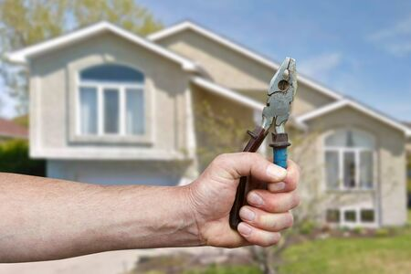 Hand of worker with pliers. Cottage repair Stock Photo