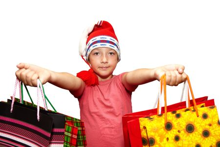 Little girl in red cap with shopping bags. Isolated over white background. Christmas Stock Photo
