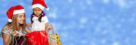 Two little girls in fur-cap with shopping bags. Over blue background. Christmas Stock Photo