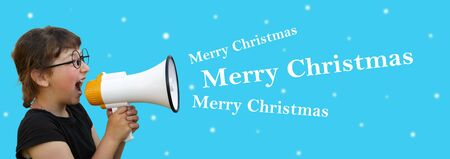 Little girl shouting by megaphone on blue background. Christmas Stock Photo