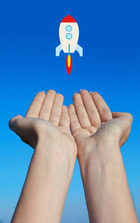 Female hands launch a rocket into the blue sky