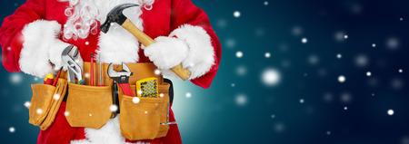 Weihnachtsmann-Arbeiter mit einem Werkzeuggürtel auf Winterhintergrund