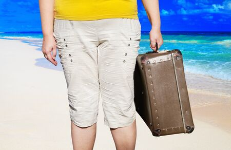 Woman with suitcases on the beach. Summer Vacation