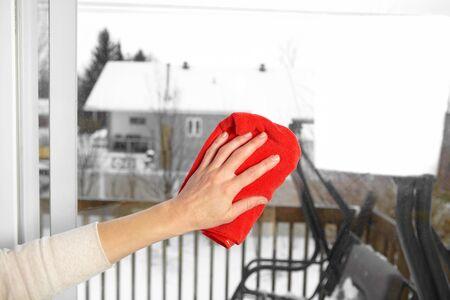 Mujer lava una ventana con un trapo