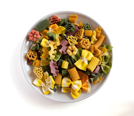 Multicolored italian pasta in plate, isolated