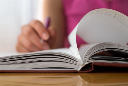 Young female opening notebook and planning her schedule. Stock Photo - 2006002