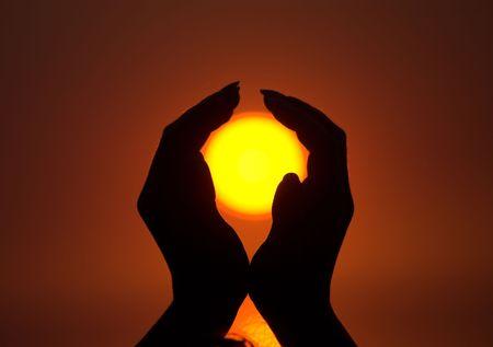 Sun in beautiful female hands during sunrise photo