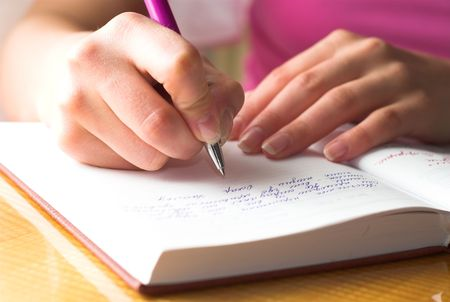 Young female is writing notes and planning her schedule. Stock Photo - 2009399