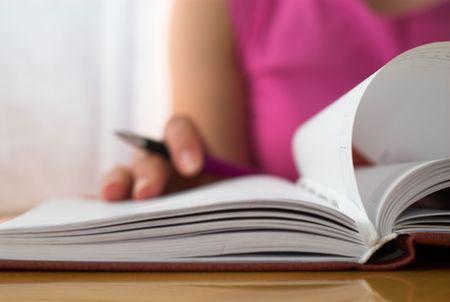 writing book: Femmina giovane sta scrivendo le note e la pianificazione i suoi impegni.
