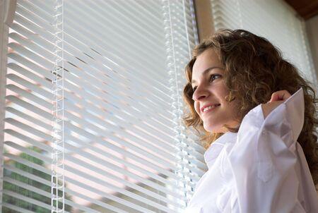 Happy woman is standing in the office near window