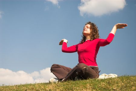 Pretty female is siiting and meditating on sky backlgroung. Stock Photo - 2171824