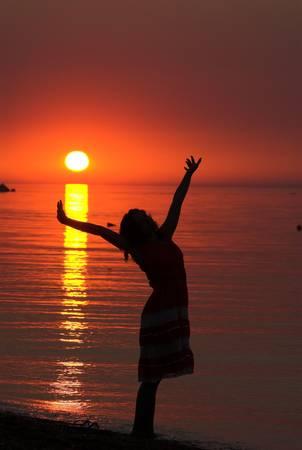 Sunrise on the sea. Silhouette of the woman photo