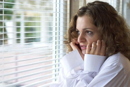 jalousie: Young female is crying near window with jalousie Stock Photo