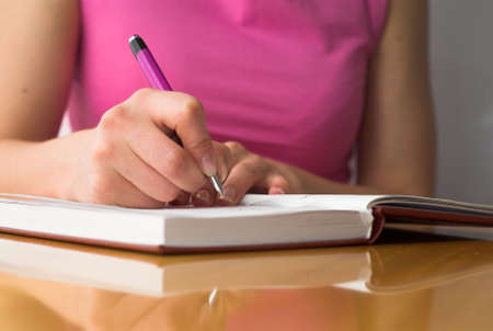 Young female is writing notes and planning her schedule. Stock Photo - 2186671