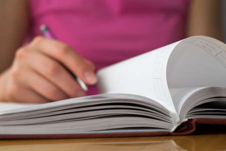 opens: Young female opens notebook and planning her schedule.