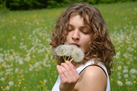 squint: Young woman with three dandelions Stock Photo