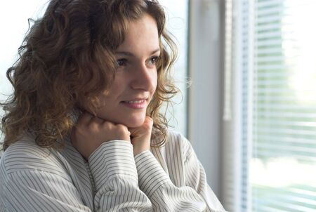 agitation: Young female is waiting with hope near window Stock Photo