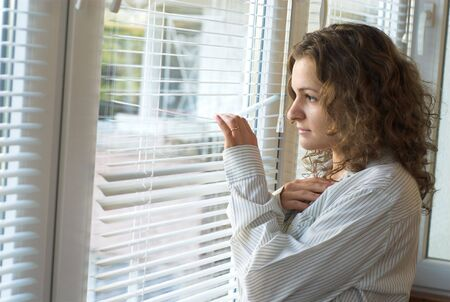 waiting glance: Young female is waiting with hope near window Stock Photo