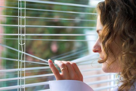 angst: Young female is waiting with hope near window Stock Photo