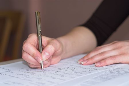 Female student is taking test in math. Fingers in focus. photo
