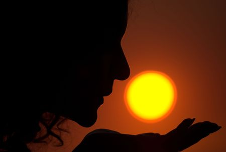 Young female is kissing the Sun during sunrise photo
