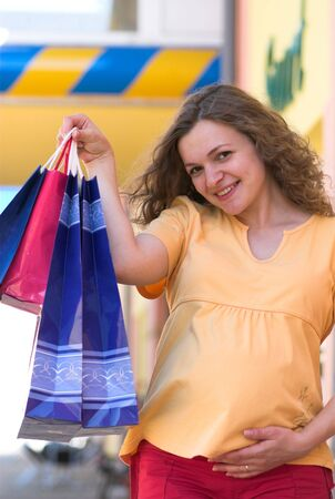 Young pregnant woman shows shopping bags photo