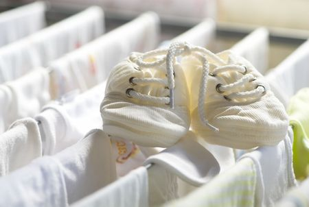 draining: Babys boots on draining board with linen Stock Photo