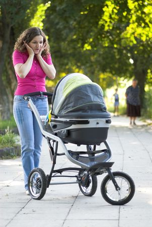 Young mother is reacting on her  in carriage photo