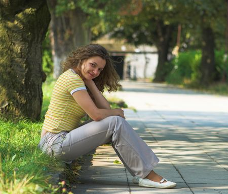 kerb: Young girl is sitting on kerb in the park