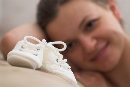 bootees: Young pregnant girl looks at babys bootees