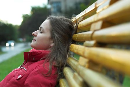 Depressed young woman is sitting on the bench Stock Photo
