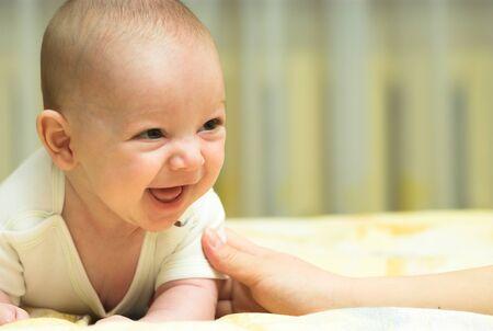 ni�os riendose: Beb� se est� riendo en una cama