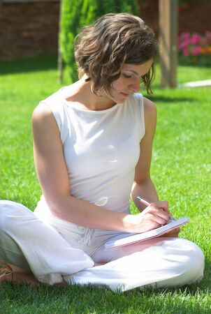 Young student is making notes on campus grass photo