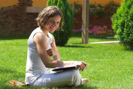 Young student with thumb up on campus lawn photo