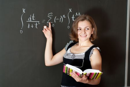 Young teacher is standing near blackboard in classroom photo