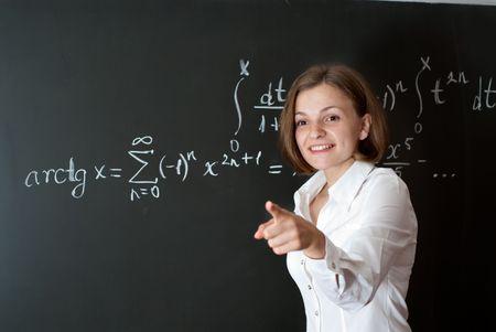 tutor: Profesor joven est� de pie cerca de pizarra en el aula de