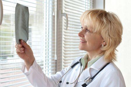 Mature doctor examining X-ray  image near window Stock Photo