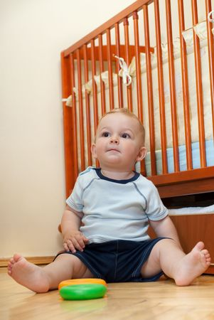 Cute child is playing near his bed Stock Photo - 5495549