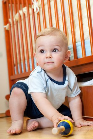 Liitle boy is sitting near his bed Stock Photo - 5495532