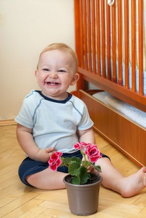 Laughung boy is sitting near his bed with flower photo