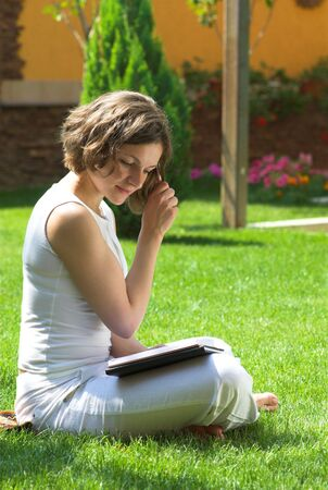 Young student is reading book on campus grass photo