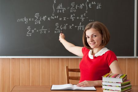 Young teacher is pointing on blackboard with math formulas photo