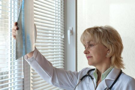 Mature doctor examining X-ray image near window photo