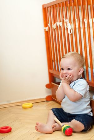 Liitle boy is sitting near his bed Stock Photo - 5620834