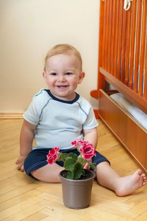Liitle boy is sitting near his bed with flower photo