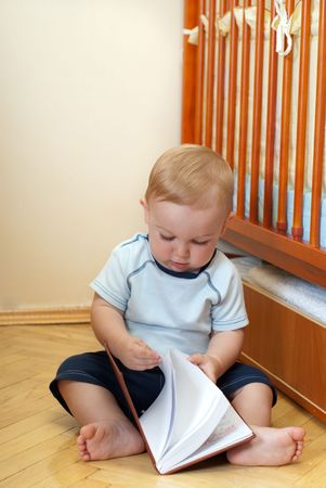 Little boy is reading book near his bed photo