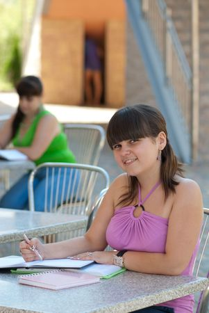 Two young students studying in campus cafe photo