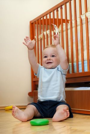 Cute boy is sitting near his bed with hands up Stock Photo - 5807264