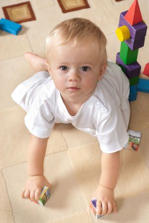 Little boy is crawling in playroom. Portrait shot Stock Photo - 5807277
