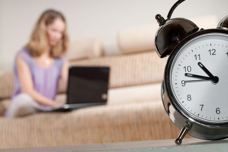 assignment: Young female is in hurry to complete urgent assignment. Primary focus on metallic alarm clock.